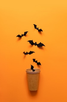Halloween holiday concept of black bats fly out of paper cup on orange surface