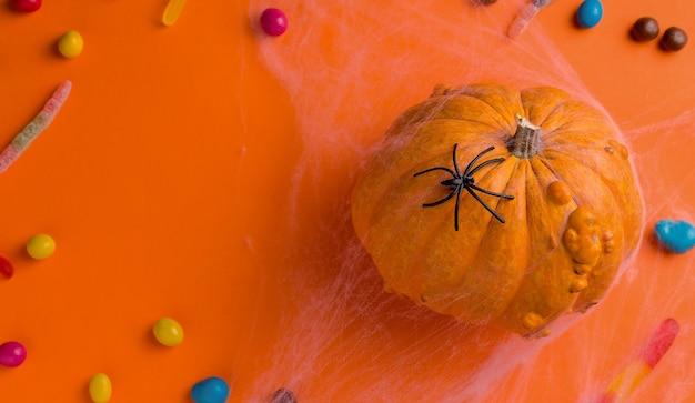 ハロウィーンの休日のコンセプト。オレンジ色の背景に、カボチャとお菓子。上からの眺め。コピースペース