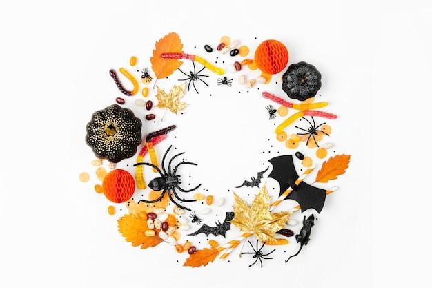 흰색 바탕에 화려한 사탕, 박쥐, 거미, 호박, 장식이 있는 할로윈 휴일 프레임입니다. 플랫 레이. 위에서 보기