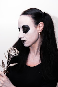 Halloween holiday, portrait of a girl with makeup holding a metallic rose flower.