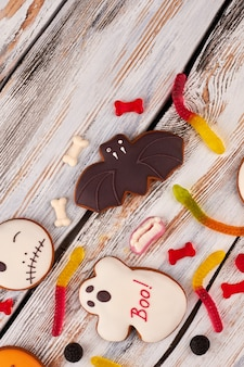 Halloween holiday sweets on wooden background.