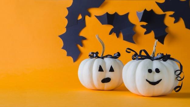 ハロウィーンの休日。オレンジ色の背景に2つの白いカボチャ、ミニマリズム