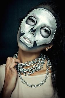Хэллоуин, праздники, образ жизни, люди, красота, креативная концепция - тема хэллоуина и креативного макияжа: красивая девушка-модель с черным телом с серебряной маской и краской черепа на темном фоне в студии