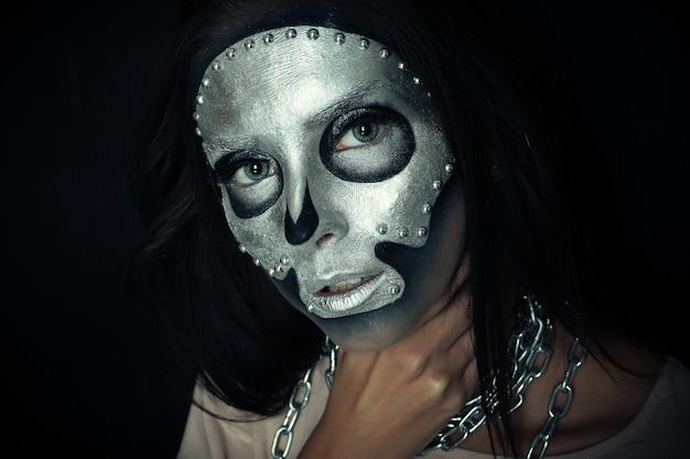 할로윈, 휴일, 라이프스타일, 사람, 아름다움, 창의적인 개념 - 할로윈 및 창의적인 메이크업 테마: 스튜디오의 어두운 배경에 은색 마스크 두개골 페인트가 있는 검은색 몸을 가진 아름다운 소녀 모델