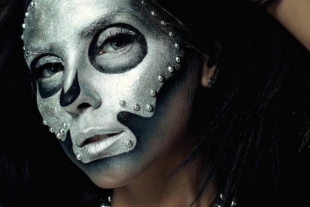할로윈, 휴일, 생활 방식, 사람, 아름다움, 창의적인 개념 - 할로윈 및 창의적인 메이크업 테마: 스튜디오의 어두운 배경에 은색 마스크 해골 페인트가 있는 검은색 몸을 가진 아름다운 소녀 모델