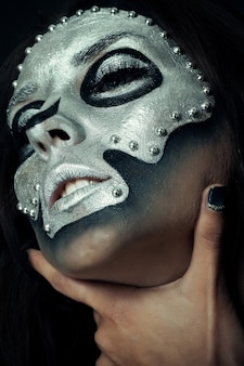 Halloween, holidays, lifestyle, people, beauty, creative concept- halloween and creative make-up theme: beautiful girl model with black body with silver mask skull paint on dark background in studio