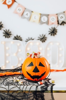 Halloween home decoration with a pumpkin basket filled with candies