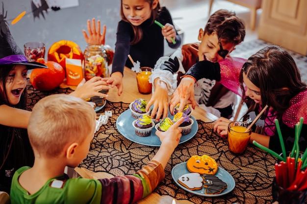 Хэллоуин в детском саду. милые дети в костюмах развлекаются во время празднования хэллоуина в детском саду