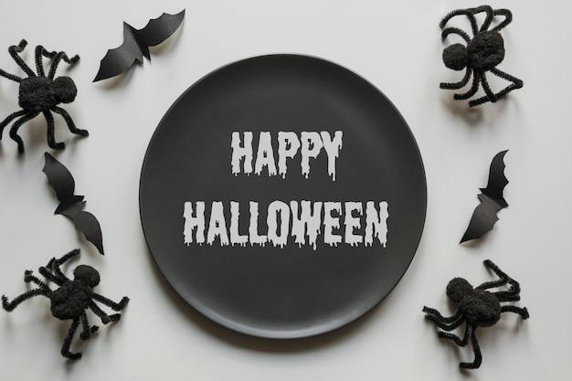 Приглашение на хэллоуин на веселую вечеринку ужасов черные пауки летучая мышь и черная тарелка с текстом счастливого хэллоуина
