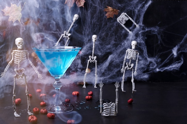 ハロウィーンは、スケルトン、クモの巣、ミニカボチャ、煙が付いた黒い背景のお祝いドリンクです。セレクティブフォーカス
