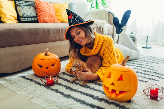 Halloween jack-o-lantern pumpkins, woman in hat playing with cat lying on carpet decorated with pumpkins and candles.