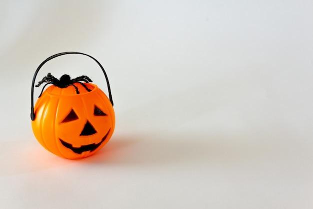 흰색 배경에 장난감 거미 복사 공간이 있는 할로윈 잭 오 랜턴 모양의 사탕 바구니