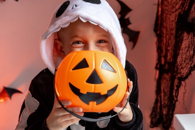 Halloween kids boy with pumpkin candy buckets in skeleton costume at home ready for trick or treat
