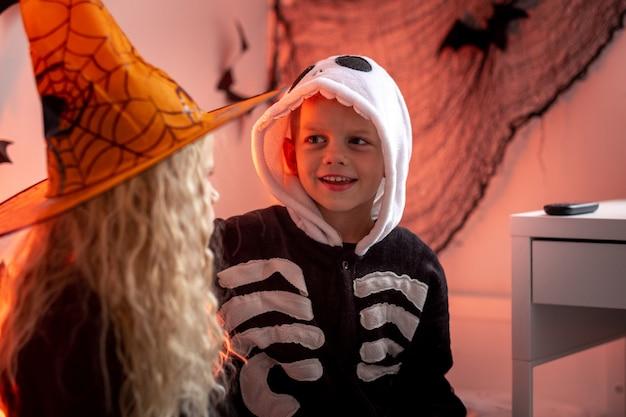 할로윈을 준비하는 할로윈 어린이 형제와 자매는 집에서 의상을 입고 소년과 소녀를 준비합니다.