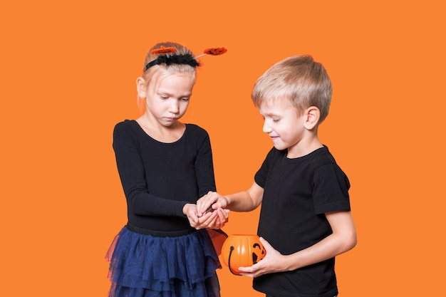 Halloween kids. children's trick or treat is a halloween tradition. boy and girl holding an orange pumpkin-shaped basket with treats in their hands on an orange background. children eat treats