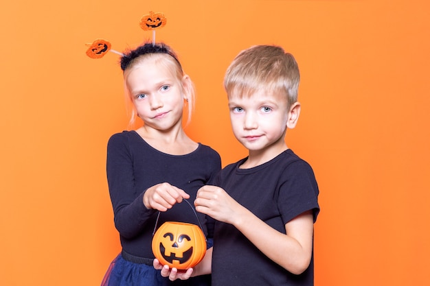 Halloween kids. children's trick or treat is a halloween tradition. boy and girl holding an orange pumpkin-shaped basket with treats in their hands on an orange background.