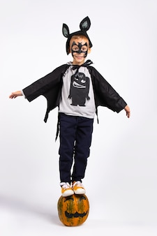 Halloween kids costume party. boy in halloween bat costume sitting on a pumpkin. isolated on white wall.