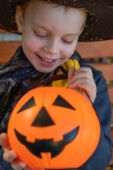 할로윈 아이들. 귀여운 소년, 주황색 사탕 양동이 잭 오 랜턴이 달린 마녀 모자를 쓴 아이. 해피 할로윈.