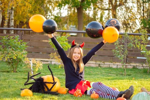 Дети хэллоуина. забавная девочка с красными рогами беса на голове сидит на траве с тыквами и большим черным пауком на открытом воздухе и держит в руках черные и оранжевые воздушные шары.