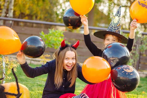 Дети хэллоуина. веселые девчонки в карнавальных костюмах сидят на траве с тыквами и большим черным пауком под открытым небом и держат в руках черные и оранжевые воздушные шары.