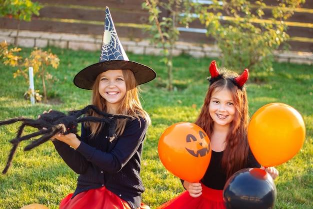 Дети хэллоуина. веселые улыбающиеся девушки в карнавальных костюмах сидят на траве с тыквами, большим черным пауком и воздушными шарами под открытым небом.
