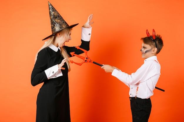 Дети хеллоуина в пугающих костюмах на оранжевой предпосылке стены. фото высокого качества