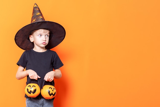 Halloween kids. little boy in a wizard's hat holding a basket in the shape of a pumpkin with sweets on an orange background, copy space. the kid wants to eat candy. halloween trick or treat tradition
