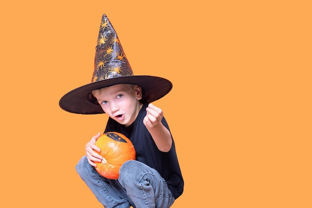 Halloween kids. little emotional boy in a wizard hat holding an orange pumpkin in his hands and showing a candy on an orange background. the kid wants to eat candy. halloween trick or treat tradition