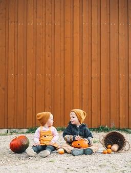 Хэллоуин детская вечеринка очаровательные дети с тыквами на деревянном фоне сарая с копией пространства
