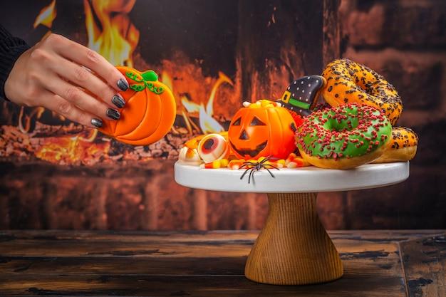 キャンディコーン、ジンジャークッキー、不気味なドーナツのハロウィーンキッズパーティーテーブル