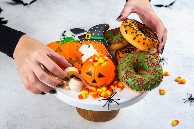 Halloween kids party table with candy corns, ginger cookies and spooky donuts.