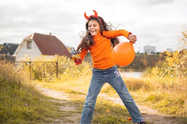 ハロウィーンの子供たち。走ってジャンプする茶色の髪の笑顔の女の子の肖像画。屋外でカーニバルの衣装を着た面白い子供たち。