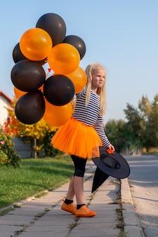 Дети хэллоуина. портрет улыбающейся девушки в шляпе ведьмы с оранжевыми и черными воздушными шарами. веселые дети в