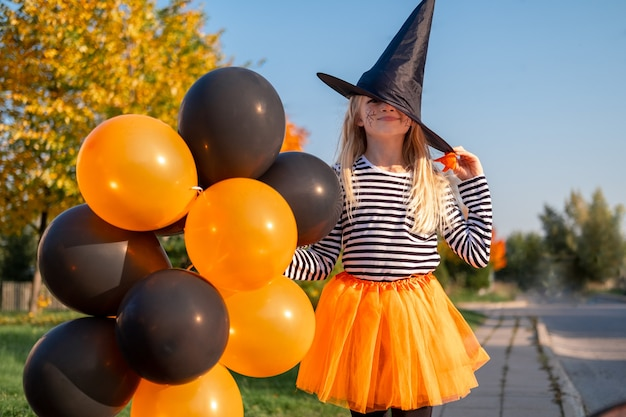 Halloween kids. portrait smiling girl in witch hat with orange and black balloons. funny kids in