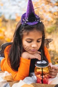 할로윈 아이들. 담요에 누워 갈색 머리를 가진 초상화 웃는 소녀. 야외에서 카니발 의상을 입은 재미있는 아이들.