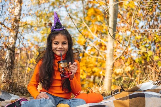 할로윈 아이들. 담요에 누워 갈색 머리를 가진 초상화 웃는 소녀. 카니발 의상을 입은 재미있는 아이들.