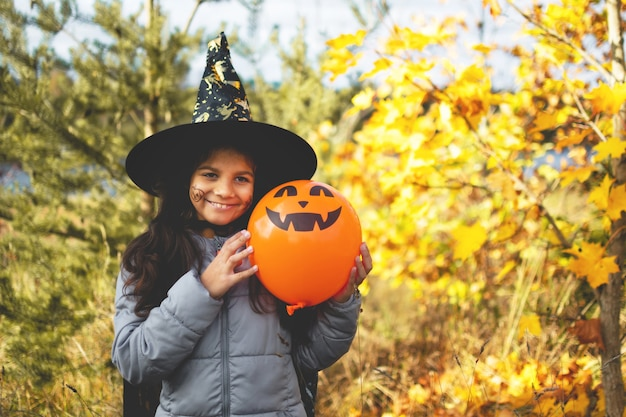 Halloween kids. portrait smiling girl with brown hair in witch hat with pumpkin balloon.
