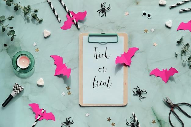 ハロウィーンlatは、ユーカリの小枝、紙コウモリ、紙吹雪、シュガーハート、パーティーの鳴り物、飲み物のストロー、ぎくしゃくした目とクモで横たわっていました。
