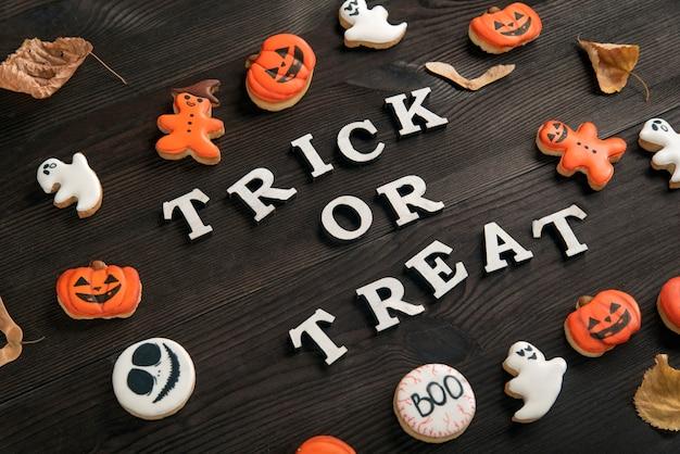 Макет на хэллоуин из белого и оранжевого вкусного имбирного печенья расположен на коричневой деревянной поверхности. кошелек или жизнь