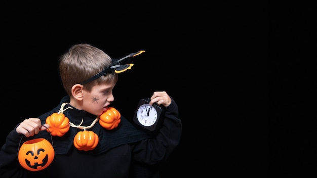 Halloween lifestyle. a boy with a spider on his cheek and a pumpkin beads holding an orange halloween basket with chocolates and a black alarm clock on a black background. time to celebrate halloween.