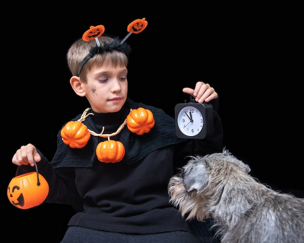 Halloween lifestyle. a boy with a spider on his cheek and a pumpkin beads holding an orange halloween basket with chocolates and a black alarm clock and a dog looking at the boy on a black background