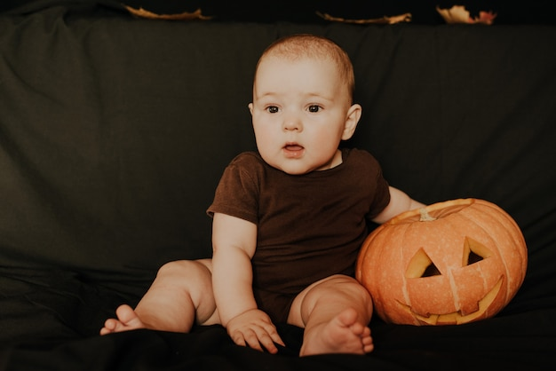Halloween. little baby boy with pumpkin jack