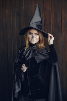 Halloween make-up beautiful woman with blond hairstyle. model girl in black costume. halloween theme.