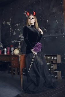 ハロウィーンメイクアップブロンドの髪型と美しい女性。黒い衣装のモデルの女の子。ハロウィーンのテーマ。