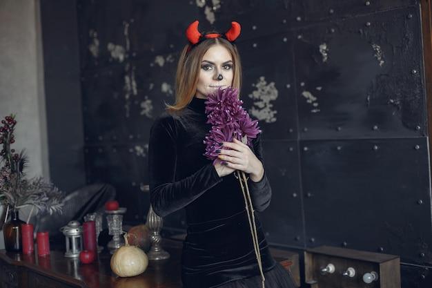 Состав хеллоуина красивая женщина с белокурой прической. модельная девушка в черном костюме. тема хэллоуина.