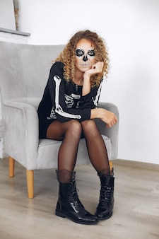 Halloween make-up skull beautiful woman with blond hairstyle. santa muerte model girl in black costume.