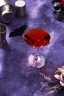 紫色の背景にハロウィーンのマティーニカクテル