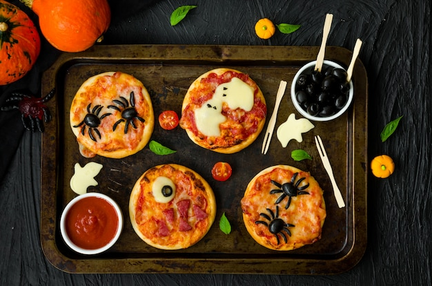 Halloween mini pizza monsters on a black background. spider pizza, ghost pizza, monster pizza. food idea for halloween party.