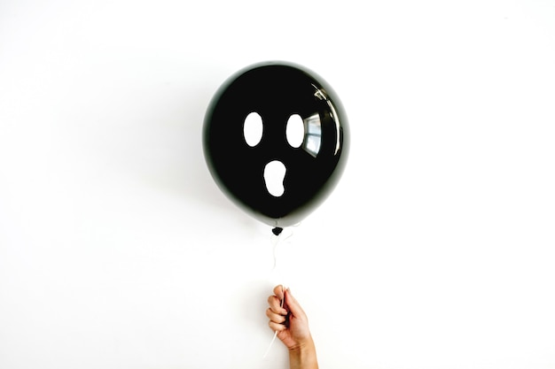 Halloween minimal concept. one black balloon with scary face in girl's hand