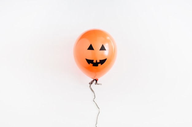Halloween minimal concept. one orange balloon with funny smiling face on white